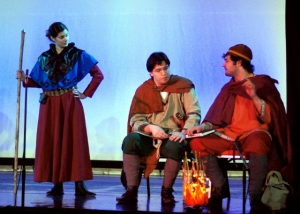 Scene from a play: two men dressed in different styles seated at a fire in conversation, while a woman holding a staff stands to the left and looks on.